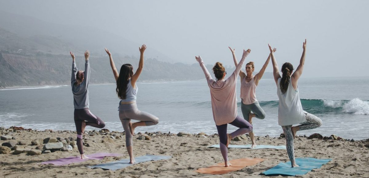 Women doing yoga on the beach together - SECCO Wine Club